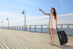Beautiful woman girl sea mooring suitcase on a pier Royalty Free Stock Images