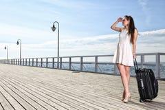 Beautiful woman girl sea mooring suitcase on a pier Stock Photo