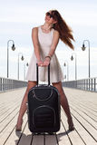 Beautiful woman girl sea mooring suitcase on a pier Royalty Free Stock Image