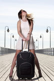 Beautiful woman girl sea mooring suitcase on a pier Royalty Free Stock Photos