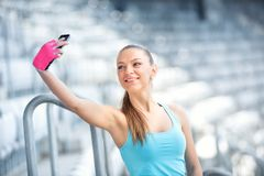 Beautiful woman, girl taking selfies while training. Fitness concept with smartphone, girl and workout Royalty Free Stock Image