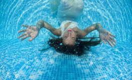 Beautiful woman girl white dress underwater diving swim blue sunny day pool Royalty Free Stock Images