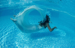 Beautiful woman girl white dress underwater diving swim blue sunny day pool Royalty Free Stock Photos