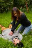 Beautiful woman giving first aid to a handsome young man, cardiopulmonary resuscitation, in a grass background Stock Photo