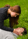 Beautiful woman giving first aid to a handsome young man, cardiopulmonary resuscitation, in a grass background Royalty Free Stock Photography