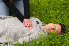 Beautiful woman giving first aid to a handsome young man, cardiopulmonary resuscitation, in a grass background. Beautiful women giving first aid to a handsome stock photo