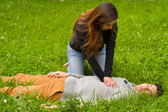 Beautiful woman giving first aid to a handsome young man, cardiopulmonary resuscitation, in a grass background Royalty Free Stock Image