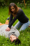 Beautiful woman giving first aid to a handsome young man, cardiopulmonary resuscitation, in a grass background Stock Photography
