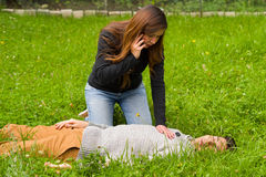 Beautiful woman giving first aid to a handsome young man and using her cellphone to call the ambulance, cardiopulmonary Royalty Free Stock Photo