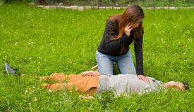 Beautiful woman giving first aid to a handsome young man and using her cellphone to call the ambulance, cardiopulmonary Stock Photo