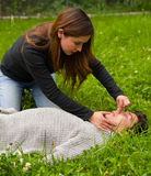 Beautiful woman giving fisrt aid to a handsome young man, cardiopulmonary resuscitation, in a grass background Royalty Free Stock Photography