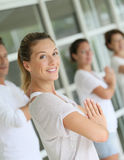 Beautiful woman giving a group of people yoga course. Attractive blond women attending yoga course with group Stock Photo