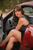 Beautiful Woman Glances out of Red Car Stock Images