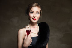 Beautiful woman with glass red wine. Retro style Stock Image
