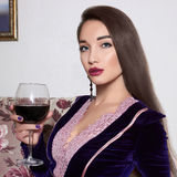 Beautiful woman with glass of wine. Beautiful woman with a wine glass in an interior Stock Image