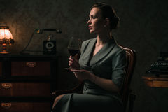 Beautiful woman with glass of wine in retro interior Royalty Free Stock Photo