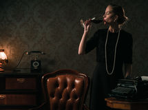 Beautiful woman with glass of wine in retro interior Stock Photos
