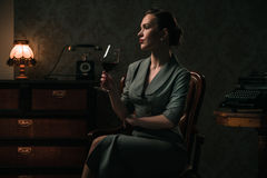 Beautiful woman with glass of wine in retro interior. Beautiful young woman in retro interior stock photography