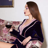 Beautiful woman with glass of wine. Beautiful young woman on a luxury sofa with a glass of wine Stock Images