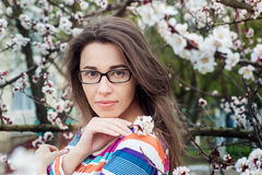 Beautiful woman in glasses on a background of a blossoming tree Stock Photos