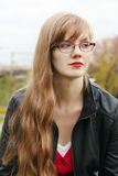 Beautiful woman in glasses in leather jacket looks away Royalty Free Stock Photos