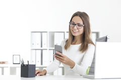 Beautiful woman in glasses with phone in office royalty free stock photography