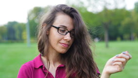 Beautiful woman in glasses posing in the summer park.  stock video footage