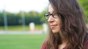 Beautiful woman in glasses posing in the summer park.  stock video