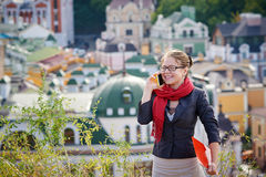 Beautiful woman in glasses with red folder on the phone against summer buildings Royalty Free Stock Photos
