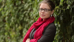 Beautiful woman in glasses and red scarf posing on a background of green leaves stock video