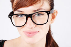 Beautiful woman in glasses smiles and looks at camera. Beautiful woman in big black glasses smiles and looks at camera Royalty Free Stock Photo