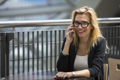 Beautiful woman in glasses talking on the cell phone sitting at a table in the Mall. Royalty Free Stock Photography