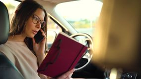 Woman in glasses speaks on the smartphone and drinks coffee in the car. Beautiful woman in in glasses talking on the smartphone and drinking coffee in the car stock video footage
