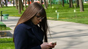 Beautiful woman in glasses uses cell smartphone outdoors in the park  - detail . Young attractive happy girl relaxes in. Beautiful woman in glasses uses cell stock footage