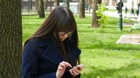 Beautiful woman in glasses uses cell smartphone outdoors in the park  - detail . Young attractive happy girl relaxes in. Beautiful woman in glasses uses cell stock video footage