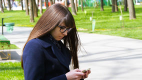 Beautiful woman in glasses uses cell smartphone outdoors in the park  - detail . Young attractive happy girl relaxes in Royalty Free Stock Image