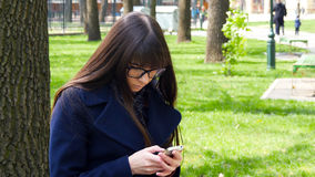 Beautiful woman in glasses uses cell smartphone outdoors in the park  - detail . Young attractive happy girl relaxes in Royalty Free Stock Photo