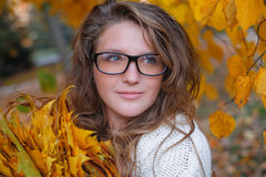 Beautiful woman with glasses walks in autumn park Royalty Free Stock Photography