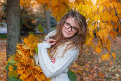 Beautiful woman with glasses walks in autumn park Stock Image