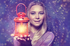 Beautiful woman with glowing lantern. Portrait of a beautiful woman holding on hand red retro style glowing lantern over night starry sky background, magical Royalty Free Stock Images