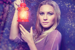 Beautiful woman with glowing lantern. Portrait of a beautiful woman with glowing lantern at nighttime, magical Christmas night, Christmastime fairytale Stock Image