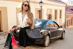 Beautiful woman goes shopping in the city with car Royalty Free Stock Images