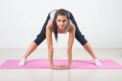 Beautiful woman goes in for sports, fitness, doing exercises with a smile, stretching. Healthy lifestyle, health. Royalty Free Stock Photos
