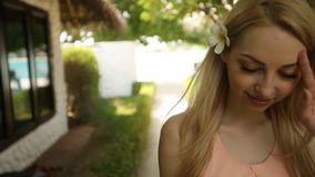 Beautiful woman goes to spa room bungalow on exotical tropical island. Smiling blonde girl walks barefoot on white sand stock footage