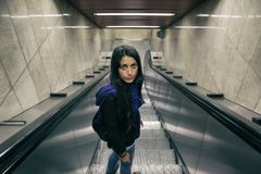 Beautiful woman going down escalator royalty free stock photo