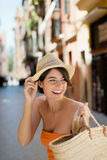 Beautiful woman going out shopping. In a trendy summer dress and straw hat looking back expectantly over her shoulder with a smile waiting for somebody Stock Image
