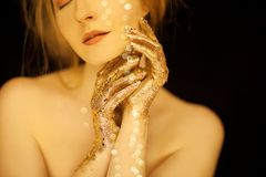 Beautiful woman in gold, golden hands, glitter sensual glamour luxury royalty free stock image