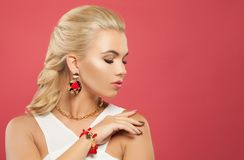 Beautiful woman in gold jewelry necklace, earrings and coral bracelet on pink background.  royalty free stock image