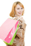 A beautiful woman in a gold suit with shopping Stock Photo