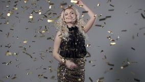 Beautiful woman among golden confetti, slow motion. stock video footage